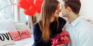 couple smiling on the couch holding valentines day presents