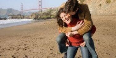 couple on the beach in san francisco goldeen gate bridge