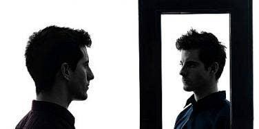 man looks in mirror