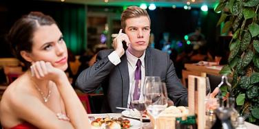 man on the phone during a dinner date