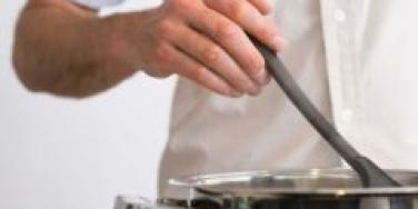 man stirring pot on stove