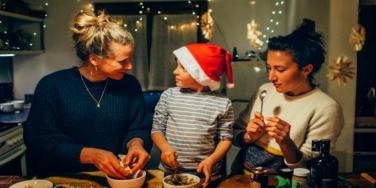grandmother and mother cooking with child in santa hat