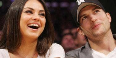 Mila Kunis and Ashton Kutcher sitting courtside at a basketball game