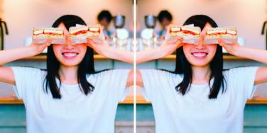 woman holding sandwich halves above her eyes