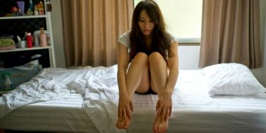 young woman with brown hair sits on the edge of the bed looking depressed