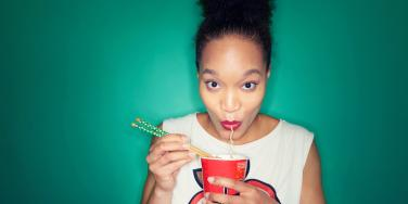 woman eating noodles with a green background