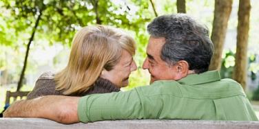 old couple sitting on a park bench