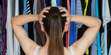 frustrated woman with hands on head in front of clothing in closet