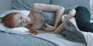 woman in bed with menstrual cramps
