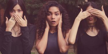 three women covering mouth, ears, and eyes