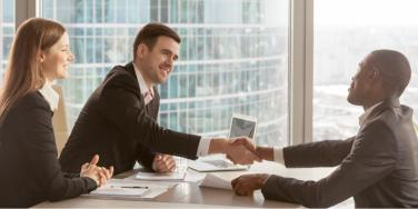people shaking hands in business setting