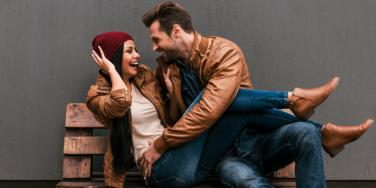 man and woman cuddling on bench