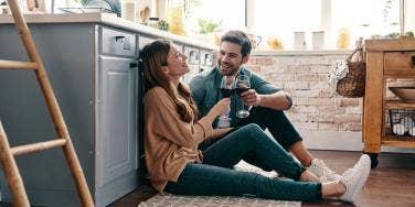 couple talking on the floor of a kitchen