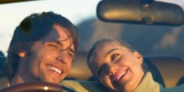 a couple laughing as they are driving in car