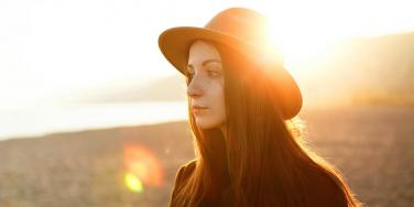 woman staring with sunset behind her