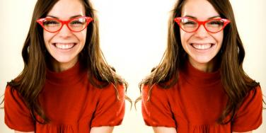 woman with red glasses smiling