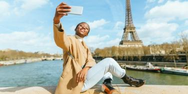 woman taking photo in front of Eiffel tower