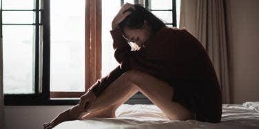 woman on floor holding her head
