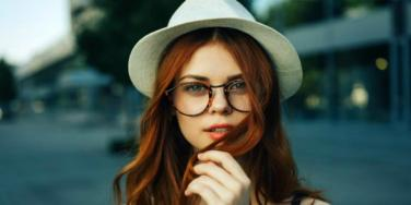 young brunette in tortoise-shell round glasses and a white hat looks into camera and coyly plays with hair