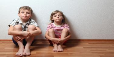 little boy and little girl sitting on floor