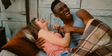 laughing couple in bed