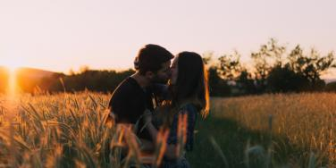 man and woman, each with brown hair, kiss in a field at sunset