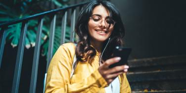 woman smiling looking at phone texting