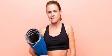 uncertain woman with yoga mat