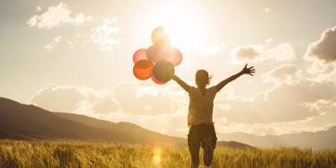 hopeful woman holding balloons while watching the sun