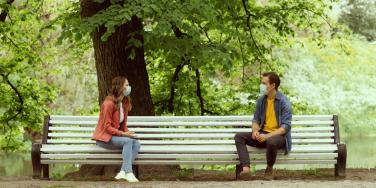 man and woman on socially distanced date in the park