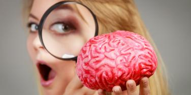 woman look at brain through magnifying glass