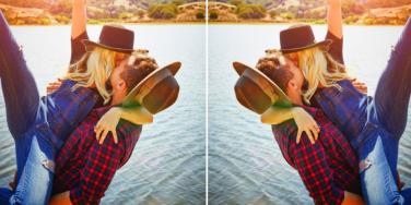 couple wearing plaid and hats kissing by the water