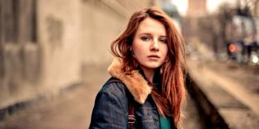 sad woman looking forward red hair jean jacket