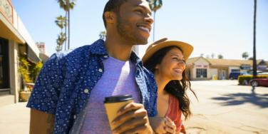 man and woman smiling holding coffee walking