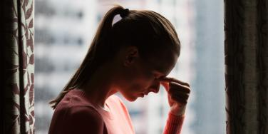 woman in ponytail pinching the bridge of her nose in front of window