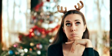 woman with reindeer antlers with christmas tree