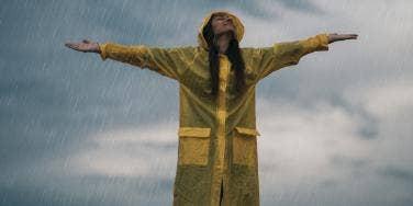 woman in raincoat standing in the rain