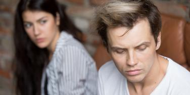 upset man looking away from woman behind him
