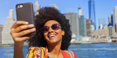 smiling woman with her phone on staycation