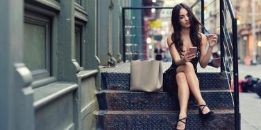 woman on her phone sitting on steps