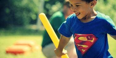 littly boy in Superman shirt playing