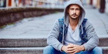man wearing a hoodie sitting on stairs