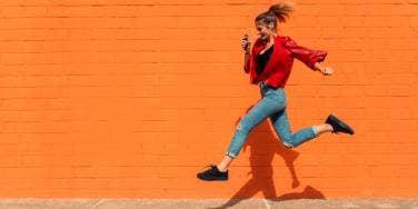 woman jumping over sidewalk crack orange background