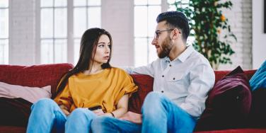 sad man and woman sitting on couch