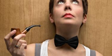 woman wearing a bowtie looking up while holding a pipe