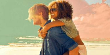 twin flame couple, woman riding on man's back, looks at sunset