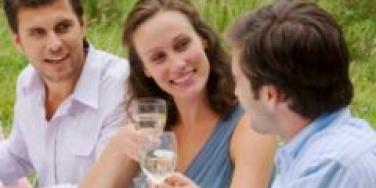 two men one woman in middle outdoor party toasting