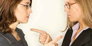 two women pointing at each other