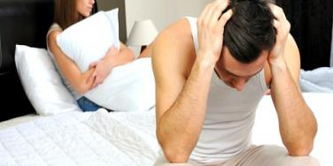 upset couple in bed.