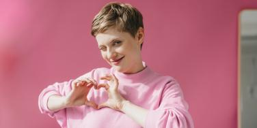 winking woman making a heart with her hands